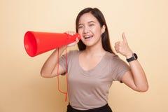 Den härliga unga asiatiska kvinnashowen tummar meddelar upp med megapho Royaltyfria Foton