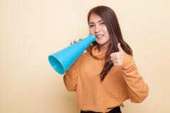Den härliga unga asiatiska kvinnashowen tummar meddelar upp med megapho Fotografering för Bildbyråer