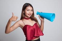 Den härliga unga asiatiska kvinnashowen tummar meddelar upp med megapho Arkivbild