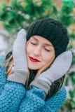 Den härliga unga blonda flickan i hatt och tumvanten täcker hans framsida utanför i förkylningen, det retro fotoet för effekt, ko royaltyfria bilder