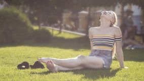 Den härliga unga blonda flickan kopplar av på ett gräs i en stad parkerar, Central Park på en solig dag Fotografering för Bildbyråer