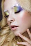 Den härliga unga blonda kvinnan med idérik sminkfärg, krullar och blommar på ögonbryn Härlig le flicka Art Makeup royaltyfri foto