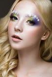 Den härliga unga blonda kvinnan med idérik sminkfärg, krullar och blommar på ögonbryn Härlig le flicka Art Makeup arkivfoto