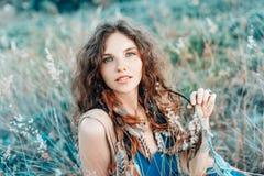 Den härliga unga bohoen utformade kvinnan på ett fält på solnedgången royaltyfria foton