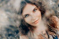 Den härliga unga bohoen utformade kvinnan på ett fält på solnedgången arkivfoto