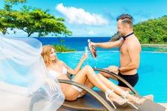 Den härliga unga bruden i en vit bikini, skyler och strumpebandet på henne Royaltyfri Fotografi