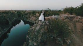 Den härliga unga bruden och brudgummen står på en klippa i bakgrunden av floden och omfamnar sig försiktigt soligt arkivfilmer