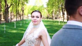 Den h?rliga unga bruden som g?r runt om brudgummen som fortfarande st?r i soligt, parkerar lager videofilmer
