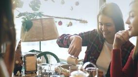 Den härliga unga brunetten häller mjölkar i en kopp kaffe stock video