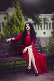 Den härliga unga brunettflickan i röd klänning sitter på en bänk Arkivfoto