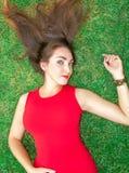 Den härliga unga brunettkvinnan ligger på gräset som lägger hennes hår, i en röd klänning royaltyfri bild