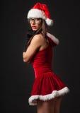 Den härliga unga brunettkvinnan med svarta retro exponeringsglas klädde som jultomten royaltyfria bilder
