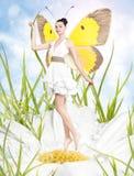 Den härliga unga kvinnan som fjäril fjädrar på tusenskönan Royaltyfri Fotografi