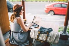 Den härliga unga caucasian valpen som sitter på en terrass i ett kafé i sommar på en trätabell i en hatt och en platta, använder  royaltyfria foton