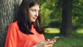 Den härliga unga damen använder smartphonen som in vilar, parkerar under träd och att tycka om den moderna teknologi- och sommarn stock video
