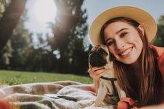 Den härliga unga damen ligger med hennes gulliga hund royaltyfri bild