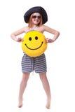 Den härliga unga elementära åldern skolar flickan med stort gult leende Royaltyfria Bilder
