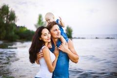 Den härliga unga familjen på semester med behandla som ett barn Fadern rymmer den blonda flickan i hennes armar, och modern för b Royaltyfri Bild