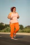 Den härliga unga feta kvinnan kör Fotografering för Bildbyråer