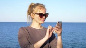 Den härliga unga flickan använder en smartphone nära havet arkivfilmer