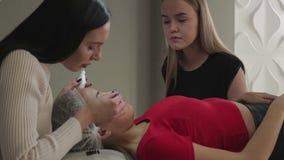 Den härliga unga flickan beundrar ögonfrans, som hennes för mycket i en skönhetsalong lager videofilmer
