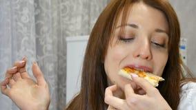 Den härliga unga flickan biter skivan av pizza med champinjoner, ost, majs, oliv, cirklar för röd lök och tomater stock video