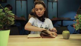 Den härliga unga flickan bläddrade till och med en bok, då plötsligt får nervös och kastade boken till golvet med henne stock video