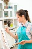 Den härliga unga flickan drar en bild målar på konstkurs royaltyfria bilder