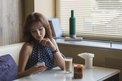 Den härliga unga flickan dricker kaffe Fotografering för Bildbyråer