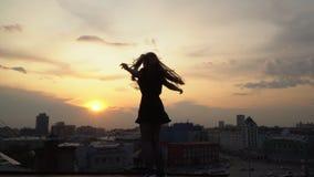 Den härliga unga flickan hoppar med de lyftta händerna och leendena mot bakgrunden av aftonstaden flickan på