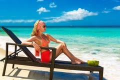 Den härliga unga flickan i bikini sitter på en soldagdrivarekust Fotografering för Bildbyråer