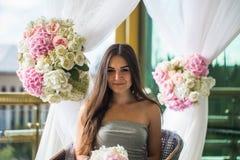 Den härliga unga flickan i grå färger klär på terrassen Royaltyfri Bild