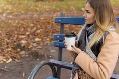 Den härliga unga flickan i höst dricker den varma drinken på stadsgatan Royaltyfria Foton