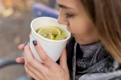 Den härliga unga flickan i höst dricker den varma drinken på stadsgatan Arkivbilder