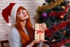 Den härliga unga flickan i jultomten cap att rymma en nea för sammanträde för gåvaask Arkivbilder