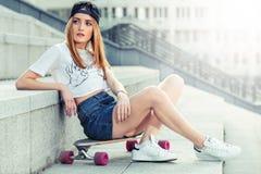 Den härliga unga flickan i kjol sitter med longboard i soligt väder Royaltyfria Bilder