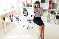 Den härliga unga flickan i kontoret sitter på skrivbordet och rymmer exponeringsglas och en telefon Royaltyfria Foton