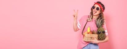 Den härliga unga flickan i rosa t-skjorta och exponeringsglas visar två fingrar, fred royaltyfri fotografi