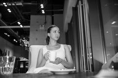 Den härliga unga flickan i den vita klänningen med den vita koppen kaffe sitter i det stads- tappningkafét och mjukheten som ser  arkivbild