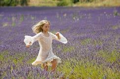 Den härliga unga flickan kör och hoppar i mitt av ett purpurfärgat fält av lavendel Arkivbilder