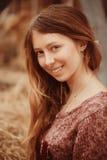 Den härliga unga flickan ler bland höet Royaltyfri Fotografi