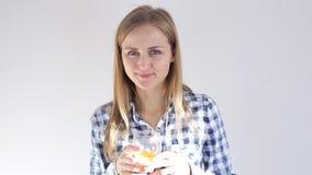 Den härliga unga flickan ler på kameran och dricker orange fruktsaft lager videofilmer