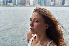 Den härliga unga flickan med brunt hår och enorma ögon på havet sätter på land i metropolisen Hong Kong royaltyfri fotografi
