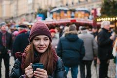 Den härliga unga flickan med en råna av den varma drinken på julen marknadsför i Dresden Fira jul i Europa arkivfoto