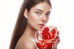 Den härliga unga flickan med ett ljust naturligt smink och gör perfekt hud med granatäpplet i hennes hand Härlig le flicka royaltyfri fotografi