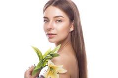 Den härliga unga flickan med ett ljust naturligt smink och gör perfekt hud med blommor i hennes hand Härlig le flicka Fotografering för Bildbyråer
