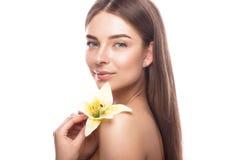Den härliga unga flickan med ett ljust naturligt smink och gör perfekt hud med blommor i hennes hand Härlig le flicka arkivbilder