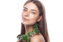 Den härliga unga flickan med ett ljust naturligt smink och gör perfekt hud med den gröna filialen i hennes hand Härlig le flicka royaltyfri fotografi