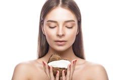 Den härliga unga flickan med ett ljust naturligt smink och gör perfekt hud med kokosnöten i hennes hand Härlig le flicka Arkivbild
