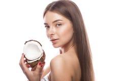Den härliga unga flickan med ett ljust naturligt smink och gör perfekt hud med kokosnöten i hennes hand Härlig le flicka fotografering för bildbyråer